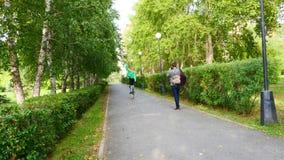 La muchacha camina a lo largo del parque en los zancos Clase de entrega almacen de metraje de vídeo