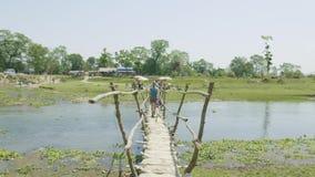 La muchacha camina a lo largo del puente de madera a través del río, Asia, Nepal almacen de video