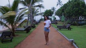La muchacha camina a lo largo del terraplén con las palmeras almacen de video
