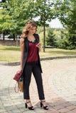 la muchacha camina a través del parque con un panier y los teléfonos fotografía de archivo