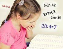 La muchacha cansó para solucionar los ejemplos en matemáticas Foto de archivo libre de regalías