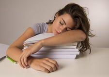 La muchacha cansada atractiva y hermosa joven del estudiante que se inclina en los libros de escuela llena dormir cansado y agota Fotografía de archivo libre de regalías