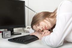 La muchacha cansada duerme en la oficina detrás de una mesa Fotografía de archivo