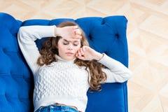 la muchacha cansada está durmiendo en el sofá en la sala de estar Foto de archivo