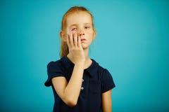 La muchacha cansada pone su mano a su cara, expresa cansancio y la fatiga, se coloca en fondo aislado azul Niño soñoliento imágenes de archivo libres de regalías