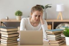 La muchacha cansada se cae el sentarse dormido en la tabla con los libros alrededor fotografía de archivo libre de regalías