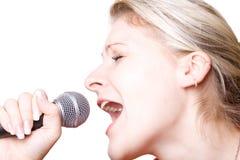 La muchacha canta con el micrófono. Fotos de archivo
