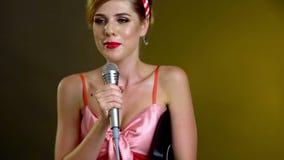 La muchacha canta con el micrófono y guarda el disco de vinilo