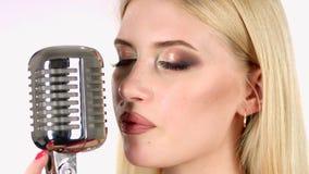 La muchacha canta en un micrófono retro Fondo blanco Vista lateral Cierre para arriba almacen de video