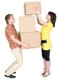 La muchacha carga al hombre con las cajas de cartón Imágenes de archivo libres de regalías