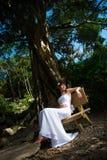 La muchacha casada se sienta en un banco en el parque en Asia imagenes de archivo