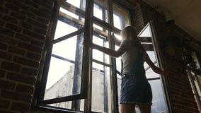 La muchacha caucásica abre la ventana por la mañana Visión trasera La muchacha hermosa delgada en guardapolvos del dril de algodó almacen de metraje de vídeo