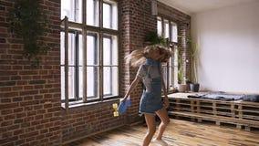 La muchacha caucásica contenta del inconformista con los auriculares alrededor del cuello está caminando con gran placer después  almacen de video