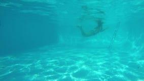 La muchacha cauc?sica corre en piscina delante de la c?mara Otra muchacha salta en piscina, sonrisas y el pulgar de las demostrac almacen de video