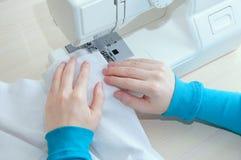 La muchacha caucásica cose la tela blanca del algodón en la máquina de coser foto de archivo libre de regalías