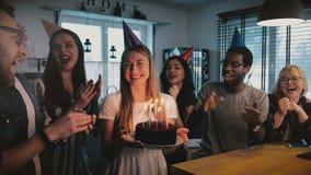La muchacha caucásica emocionada feliz que sostiene la torta de cumpleaños, los amigos multiétnicos canta una canción alegre en l almacen de video