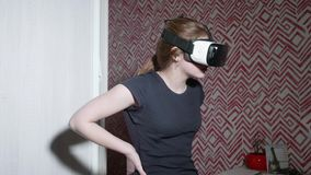La muchacha caucásica en camiseta trasera lleva los vidrios de VR y tiene gran interés en qué se está encendiendo metrajes