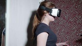 La muchacha caucásica en camiseta trasera lleva los vidrios de VR y tiene gran interés en qué se está encendiendo almacen de video