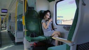 La muchacha caucásica en un sombrero viaja en tren Café de consumición de una taza de papel Ella es sola en el tren cuando él se  metrajes