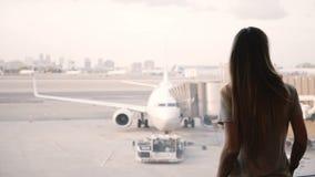 La muchacha caucásica feliz hermosa con el pelo largo camina para arriba a la ventana terminal de aeropuerto para disfrutar de la almacen de metraje de vídeo