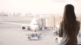 La muchacha caucásica hermosa con el pelo largo camina para arriba a la ventana terminal y a las esperas, aeroplano de aeropuerto almacen de metraje de vídeo