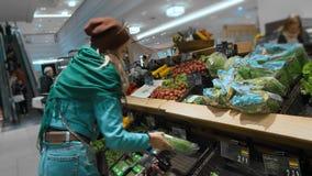 La muchacha caucásica hermosa en una chaqueta azul y una bufanda verde, elige y compra verduras verdes y productos sanos almacen de metraje de vídeo