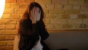 La muchacha caucásica joven con el pelo ondulado oculta su cara con las manos en miedo en fondo casero acogedor metrajes