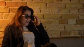 La muchacha caucásica joven con el pelo ondulado suspende sus vidrios 3D en la diversión positiva en fondo casero acogedor metrajes