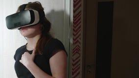 La muchacha caucásica joven en vidrios de VR parece alrededor asustada y presiona la puerta del guardarropa almacen de video