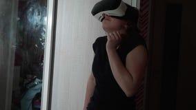 La muchacha caucásica joven en vidrios de VR parece alrededor asustada y presiona la puerta del guardarropa almacen de metraje de vídeo
