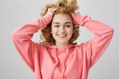 La muchacha caucásica joven positiva emotiva con free peinado, levantando el pelo con las manos y sonriendo ampliamente, expresan Foto de archivo