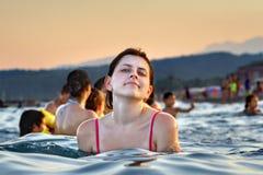 La muchacha caucásica joven se baña en la tarde del mar Foto de archivo libre de regalías