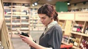 La muchacha caucásica morena hermosa joven compara dos diversas botellas de vino Elegir el vino blanco en el colmado almacen de metraje de vídeo