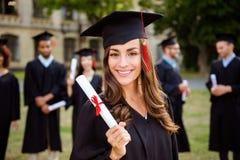 La muchacha caucásica morena linda feliz del graduado está sonriendo, los clas borrosos Fotografía de archivo