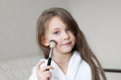 La muchacha caucásica pinta su cara con el polvo del maquillaje fotos de archivo