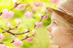 La muchacha caucásica rubia del niño admira el jardín floreciente Fotografía de archivo libre de regalías