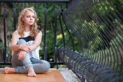 La muchacha caucásica rubia hermosa se sienta en balcón Fotografía de archivo libre de regalías