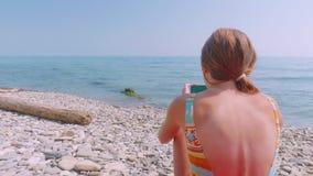 La muchacha caucásica rubia joven con un smartphone está lanzando los brazos para arriba contra el mar almacen de video