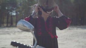 La muchacha caucásica se sienta en su motocicleta y lleva un casco Mujer de la habilidad en un vestido de cuero negro que monta u almacen de metraje de vídeo