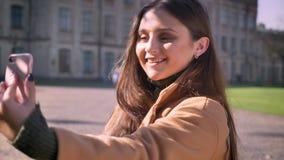 La muchacha caucásica sonriente linda está tomando selfies con sonrisa alegre y está sosteniendo su teléfono con una situación de almacen de video