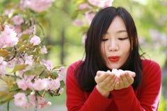 La muchacha causual descuidada libre de la belleza con las flores en parque de la primavera disfruta de tiempo libre Fotos de archivo