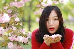 La muchacha causual descuidada libre de la belleza con las flores en parque de la primavera disfruta de tiempo libre Fotografía de archivo