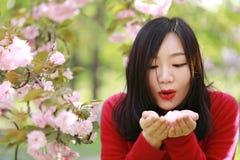 La muchacha causual descuidada libre de la belleza con las flores en parque de la primavera disfruta de tiempo libre Imagen de archivo