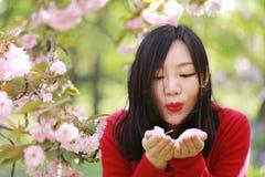 La muchacha causual descuidada libre de la belleza con las flores en parque de la primavera disfruta de tiempo libre Imagenes de archivo