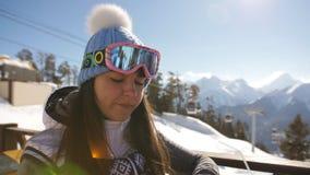 La muchacha cena en el restaurante encima de una montaña en una estación de esquí almacen de video