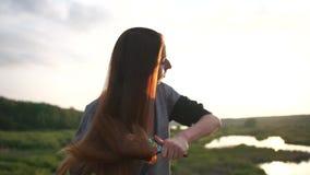 La muchacha cepilla el pelo marrón claro largo, colocándose en parque en la puesta del sol, cámara lenta almacen de video