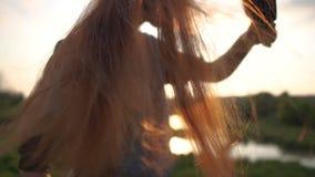 La muchacha cepilla el pelo rojo largo en el cierre de la naturaleza para arriba en la puesta del sol en la cámara lenta almacen de metraje de vídeo