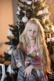 La muchacha cerca de un árbol de navidad con un conejo preferido del juguete, cajas, la Navidad, Año Nuevo, forma de vida, día de Foto de archivo libre de regalías