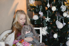 La muchacha cerca de un árbol de navidad con un conejo preferido del juguete, cajas, la Navidad, Año Nuevo, forma de vida, día de Imagen de archivo libre de regalías