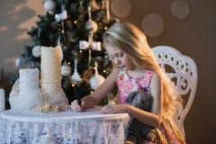 La muchacha cerca de un árbol de navidad con un conejo preferido del juguete escribe una letra a Papá Noel, cajas, la Navidad, Añ Foto de archivo